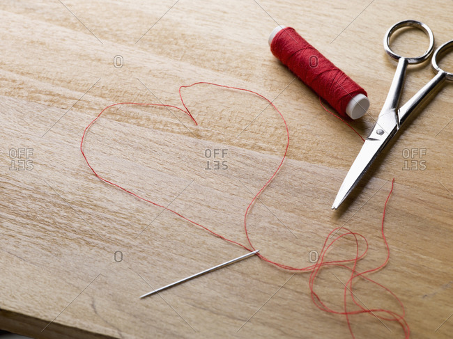 A spool of red thread, scissors, thread needle and thread shaped like a heart