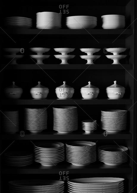 Porcelain dinnerware sets stacked on shelves.