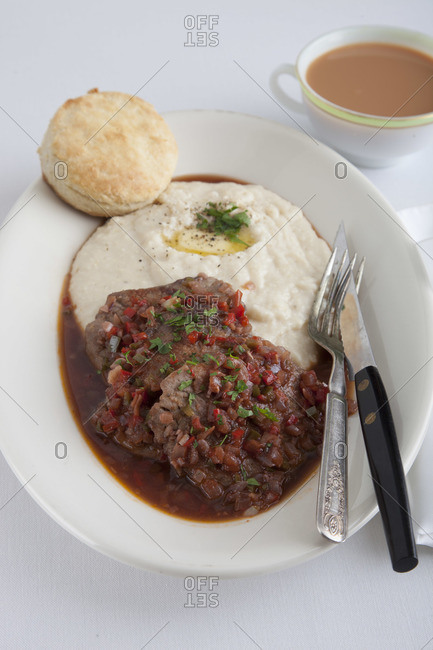 Gravy Grillades and grits served in oval-shape plate sprinkled with parsley, served with biscuit