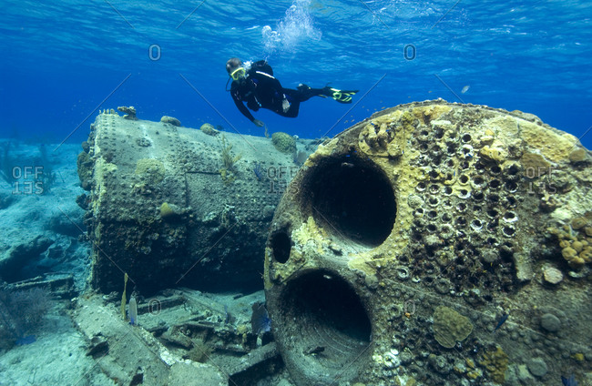 Diver swims above the boilers and other pieces of debris from the ...