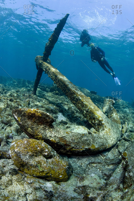 Scuba divers and large anchor on wreck site, Grand Cayman