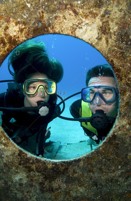Divers peer through a porthole on the sunken wreck of the Balboa, Georgetown Harbor, Grand Cayman