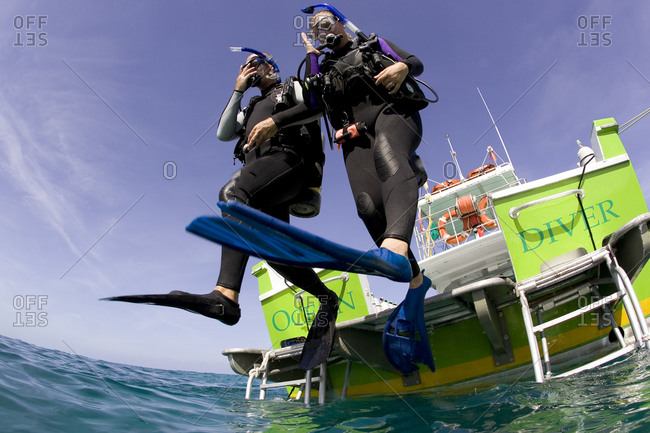 Scuba divers execute a perfect giant stride water entry into the ocean