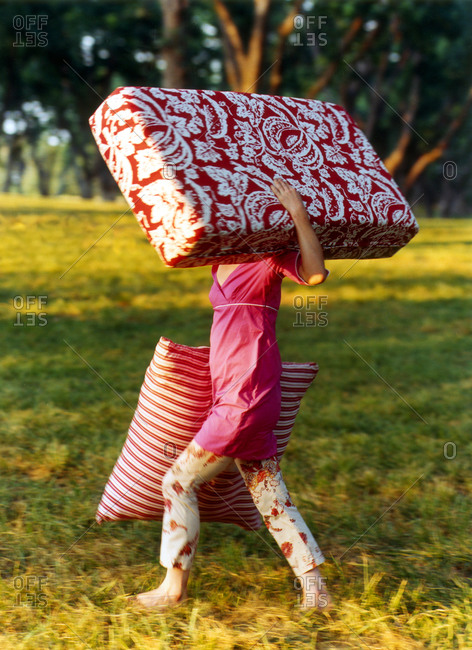 Woman carrying huge cushions