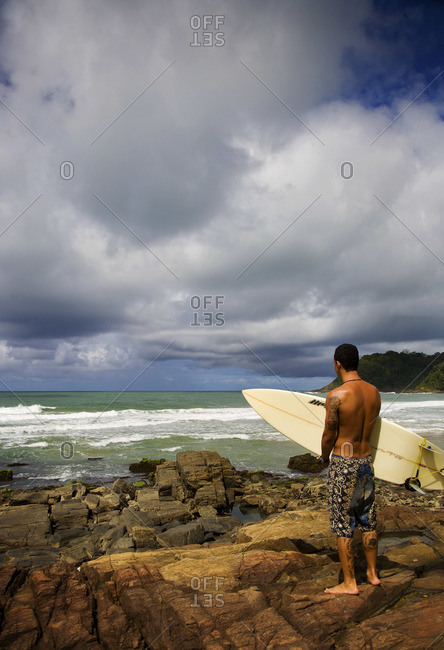 Rear view of young man with surfboard