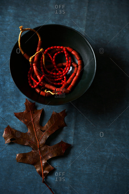 Close-up of red beaded necklace in a bowl with brown autumn leaf