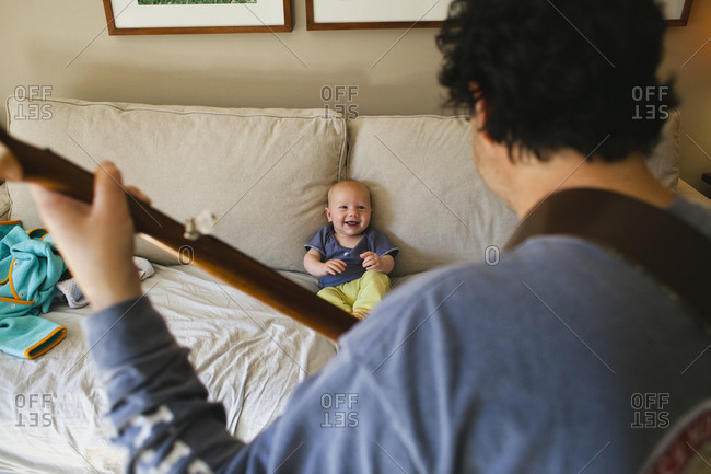 Father playing guitar to baby on couch stock photo - OFFSET
