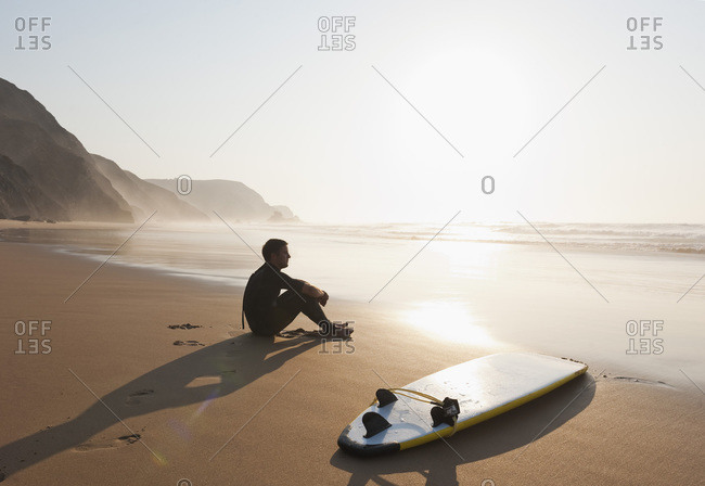 Portugal, Young man sitting on beach by surfboard