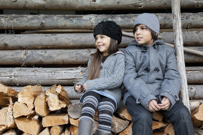 Germany, Huglfing, Girl and boy sitting on stack of firewood