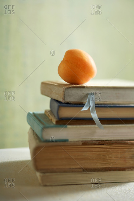 Close-up of an apricot on a stack of books