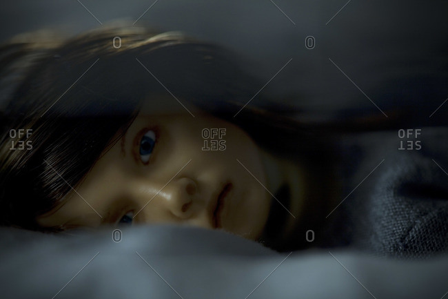 Close-up of a puppet lying in bed
