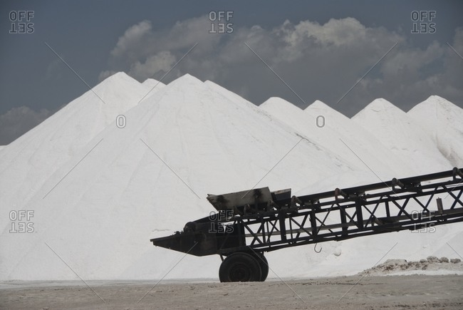 Close-up of conveyor belt with salt heaps on salt field