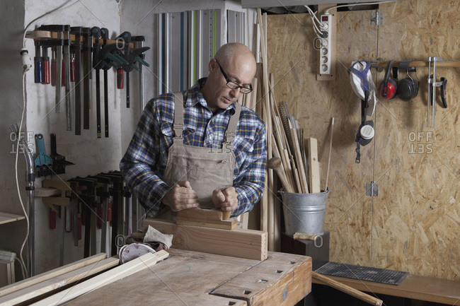 Male carpenter shaping wood in workshop