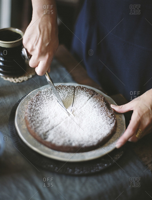 Woman slicing up chocolate cake