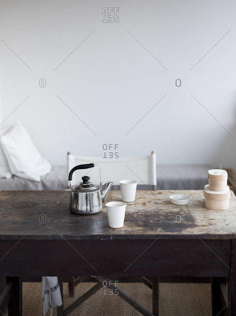 Kettle and cups on old wooden table