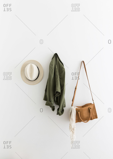 Female accessories and jacket hanging on wall