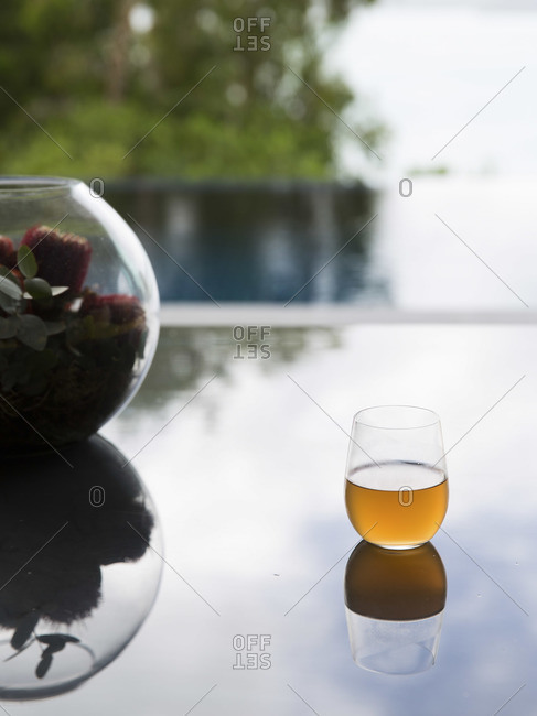 Glass of refreshment, flower arrangement and infinity pool in the background