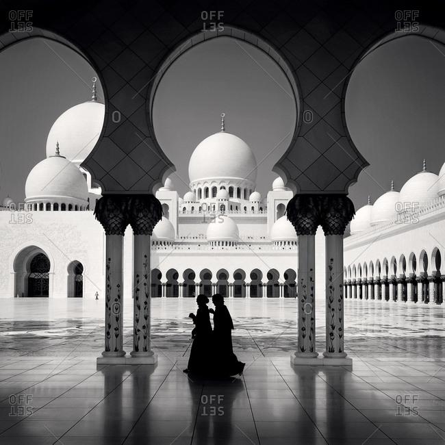 A view of two women walking through Sheikh Zayed Mosque