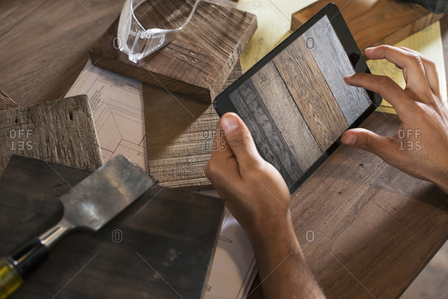 A young man in a workshop which uses recycled and reclaimed lumber to create furniture and objects, using a digital tablet