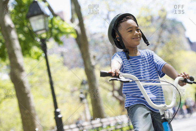 A young boy on his bicycle in the park on a sunny day