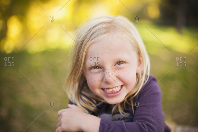A girl sitting on the grass, smiling a big toothy smile