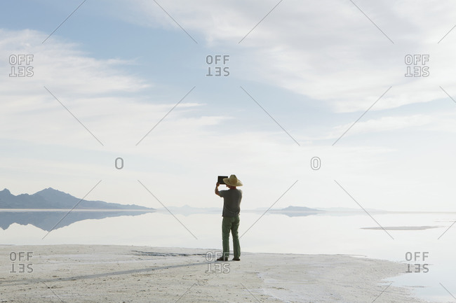 A man standing at edge of the flooded Bonneville Salt Flats at dusk, taking a photograph with a tablet device