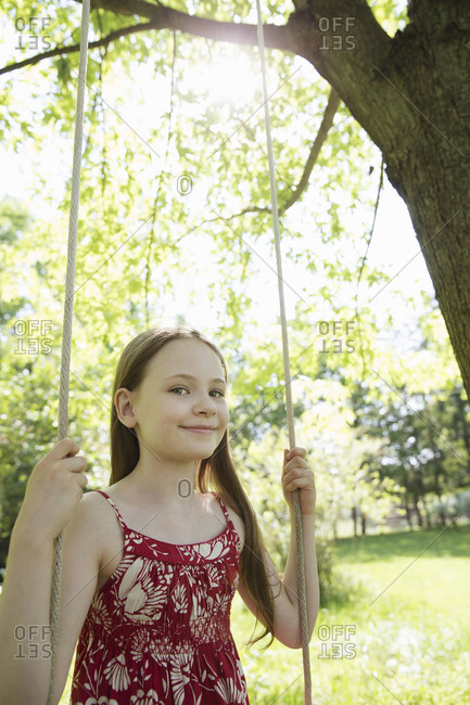 A girl in a sundress on a swing in an orchard