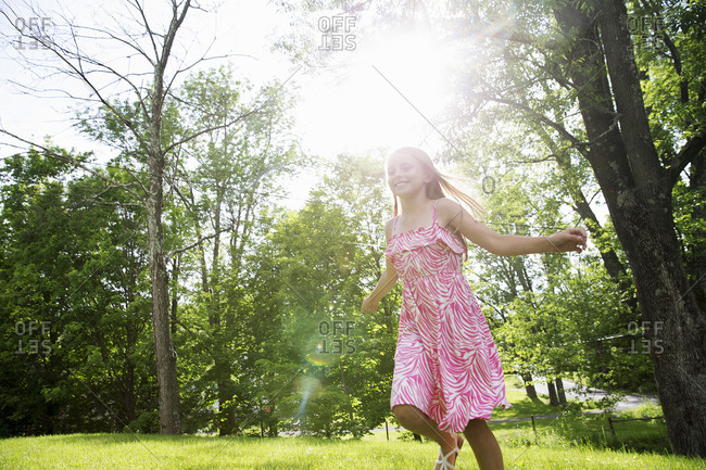 A young girl in a pink patterned sundress running across the grass under the trees in a farmhouse garden