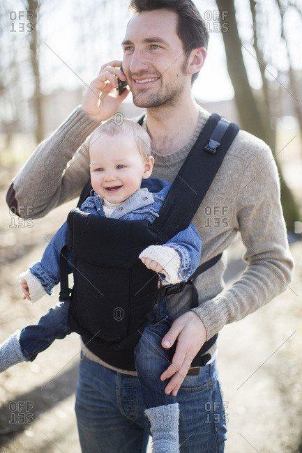Happy young man using mobile phone while carrying baby boy in carrier at field