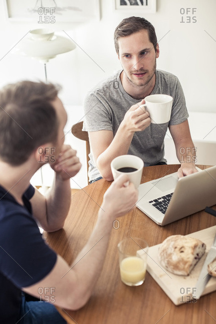 High angle view of gay couple having breakfast with laptop at table