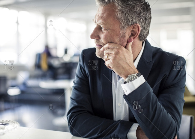 Thoughtful mature businessman looking away while sitting at desk in classroom
