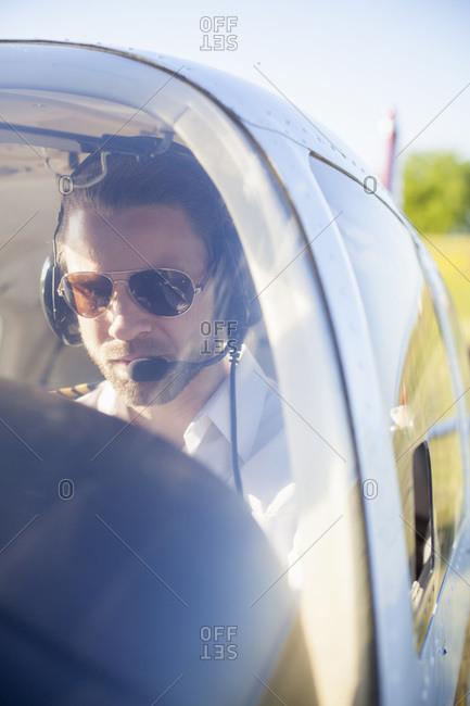 Air pilot in cockpit of propeller aeroplane