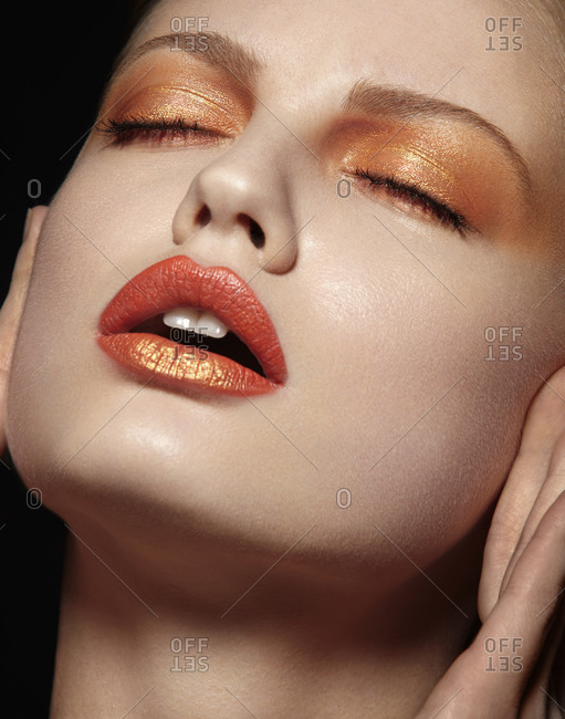 Model posing in orange eye shadow and lipstick