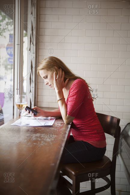 Single woman sitting in restaurant and choosing food from menu
