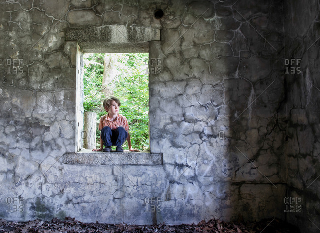 Little boy squatting on parapet of an old stone house