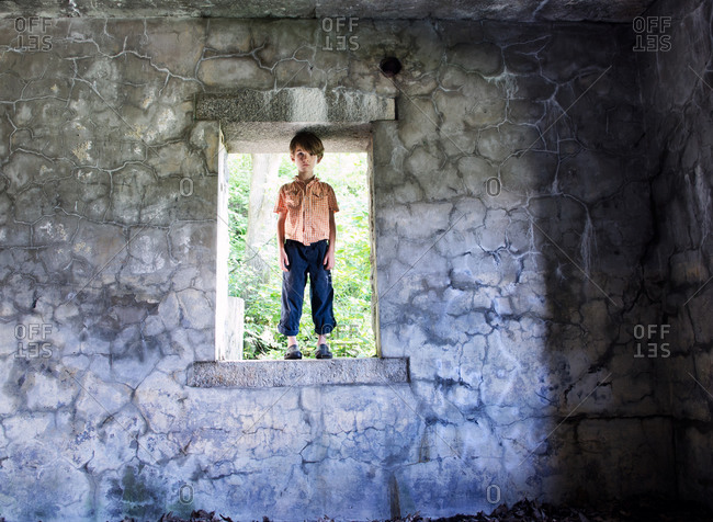 A young boy stands in an open window