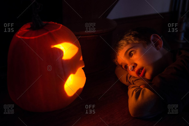 A child watches a jack o lantern