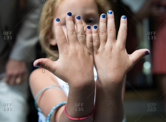 A little girl displays her nail polish