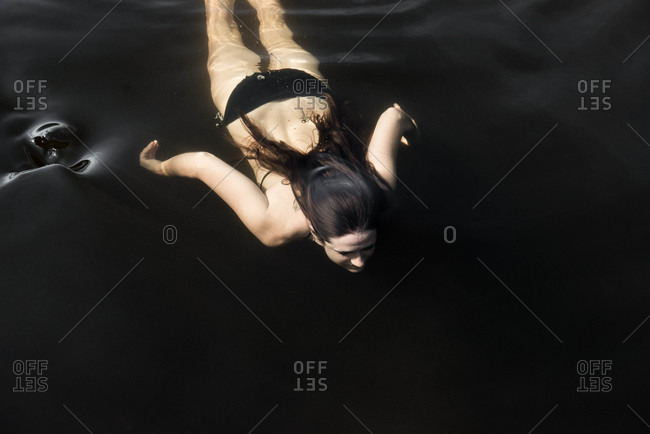 A woman swims under water