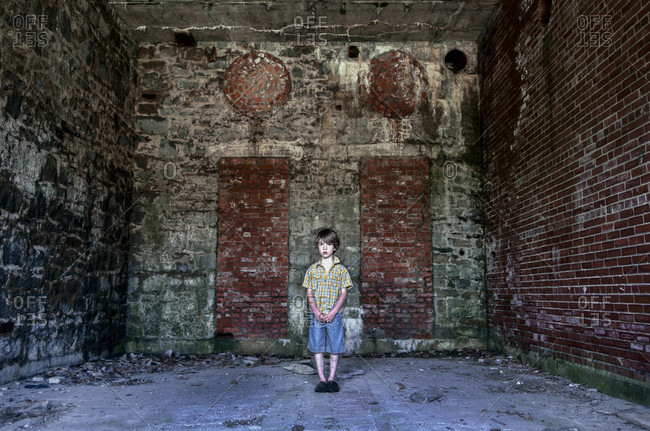 A little boy stands in a vacant brick room