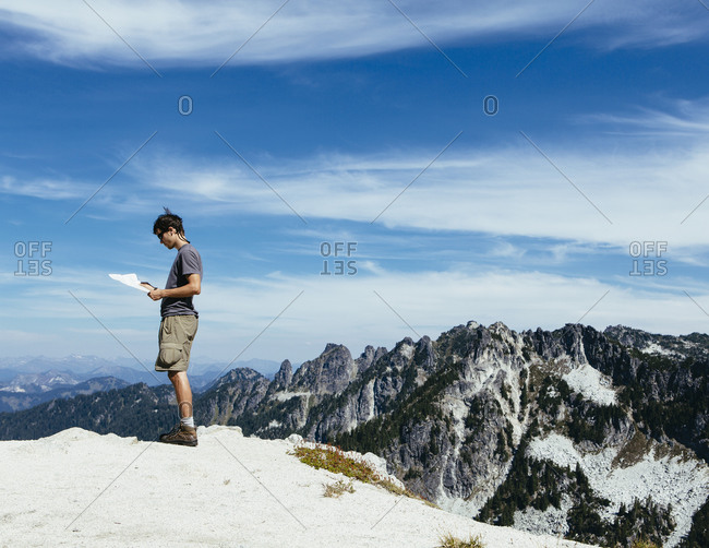 Side view of  hiker on the mountain summit, looking at a map