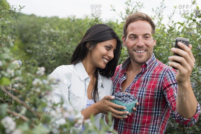 Couple among the bushes, taking a selfie with smart phone