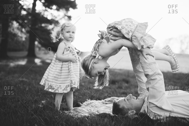 Father playing with her daughters in meadow