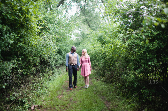 Happy young couple walking in woods