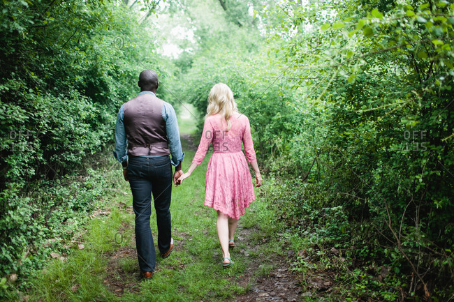Rear view of happy young couple walking in woods