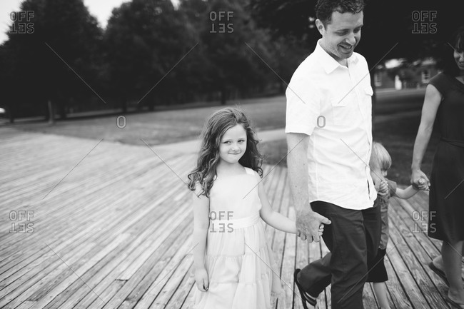 Family walking on wooden deck together, hand in hand