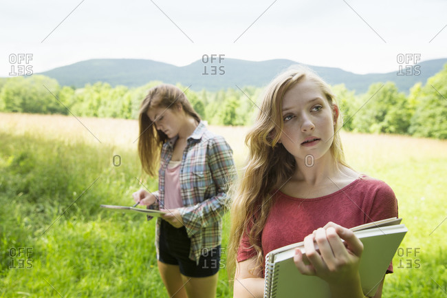 Two girls drawing on meadow