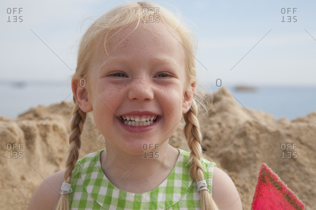 Young cheerful girl in front of huge pile of sand