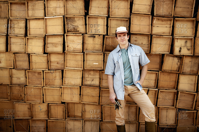 Farmer posing with piled boxes