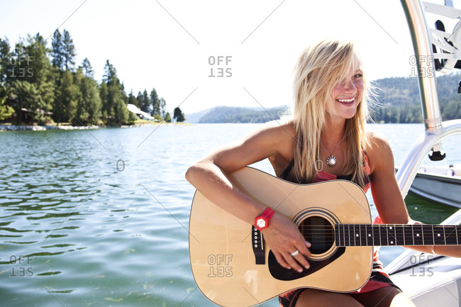 A beautiful young woman smiling plays the guitar on a wakeboard boat on a lake in Idaho